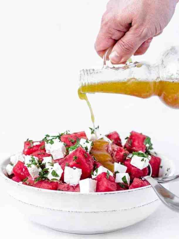 Watermelon salad with feta cheese and mint, pouring dressing onto salad