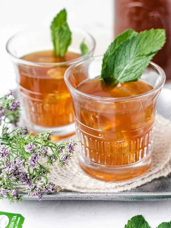 Paleo Sweet Mint Iced Tea on a tray with fresh mint leaves and tea bag in front