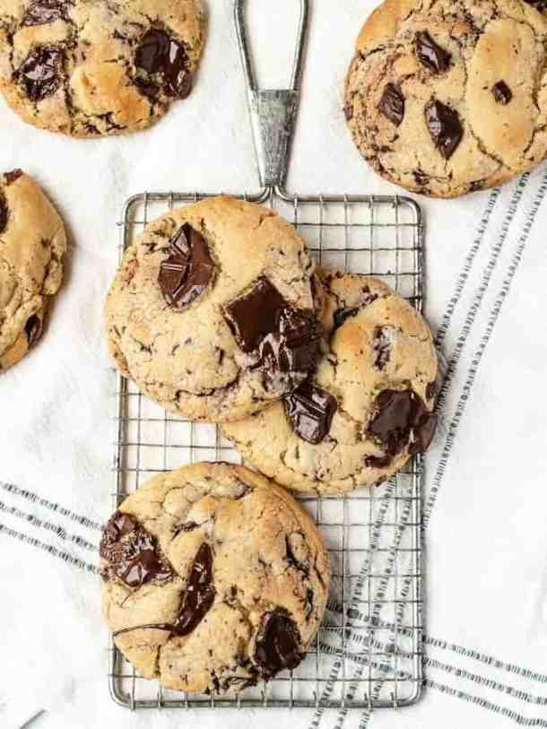 Overhead shot of big soft chocolate chip cookies on a cooling rack with more cookies surrounding