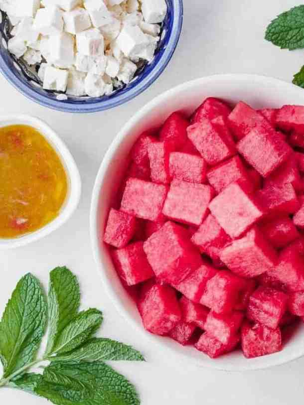 ingredients for watermelon salad laid out in bowls, shot from above, feta cheese, dressing, mint, watermelon cubed