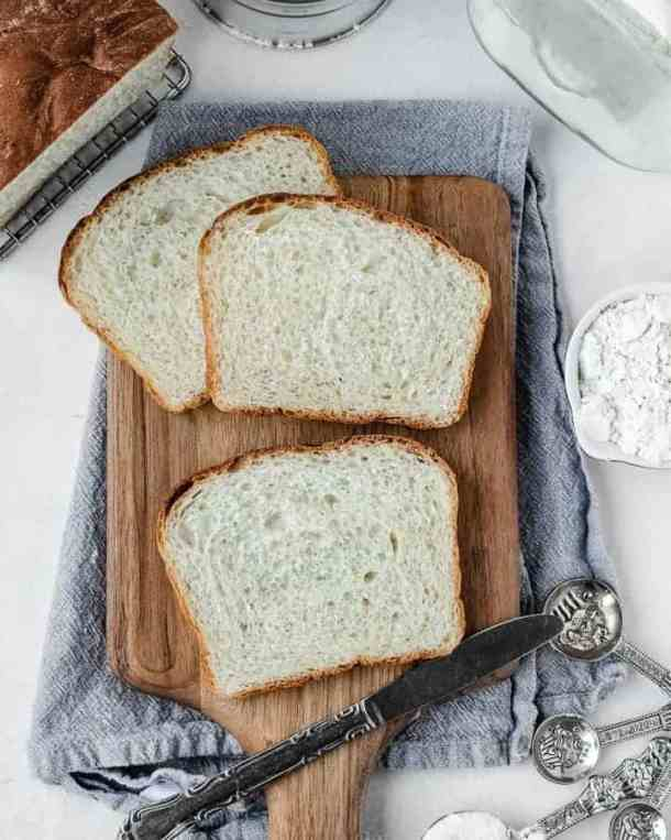 overhead photo of slices of amish white bread on a cutting board with ingredients around it