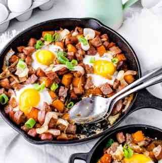 Image of caramelized onion sweet potato breakfast hash in a cast iron skillet with spoons scooping some out