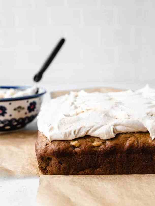 Banana Snack cake with thick layer of frosting and frosting bowl behind