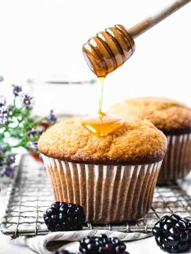 Corn muffins being drizzled with honey