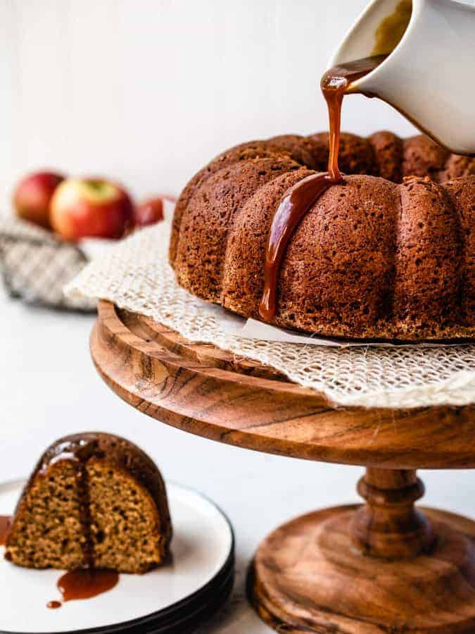 Pouring caramel sauce over applesauce bundt cake