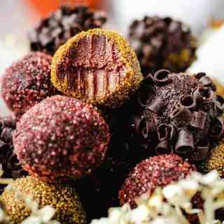 Bowl of pumpkin truffles with a bite taken out of one on top