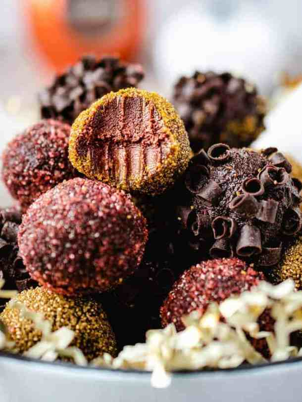 Bowl of pumpkin chocolate truffles, one on top with bite taken out