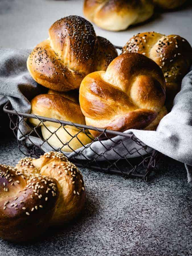 challah rolls in a bread basket with a grey napkin underneath