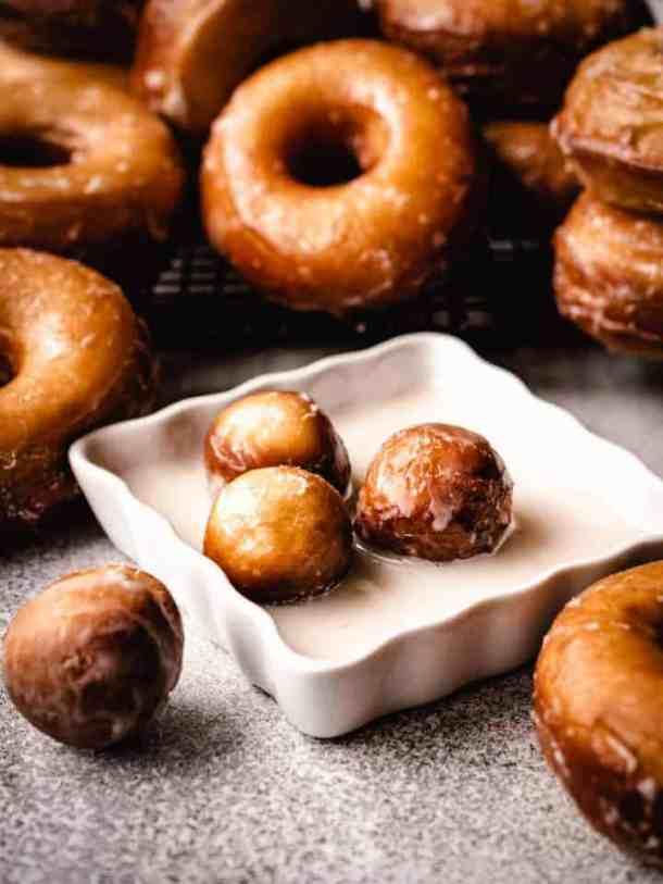 glazed donut holes sitting in glaze with donuts behind