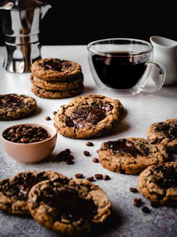espresso chocolate chunk cookies with a cup of coffee and bowl of coffee beans