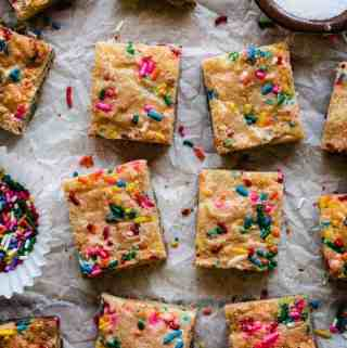 sugar cookie bars with funfetti sprinkles on a piece of parchment paper