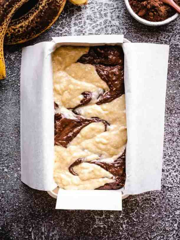 swirled chocolate banana bread batter in a loaf pan
