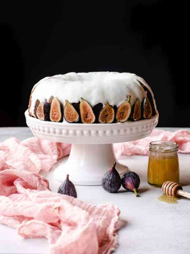 honey cake with goat cheese frosting and figs on a white cake stand