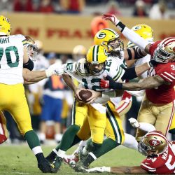 Aaron Rodgers, quarterback do Green Bay Packers sendo sackado pelo pass rush do San Francisco 49ers.
