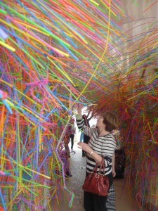 Adults adding brightly coloured straws to a plastic honeycomb tunnel