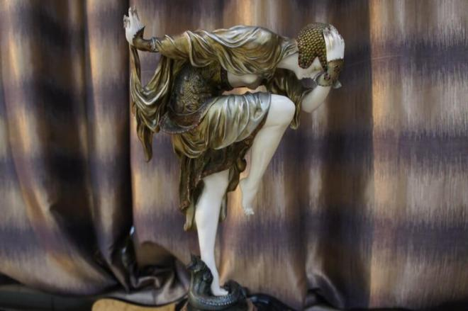 An Art Deco figurine bent over in the middle of a dance