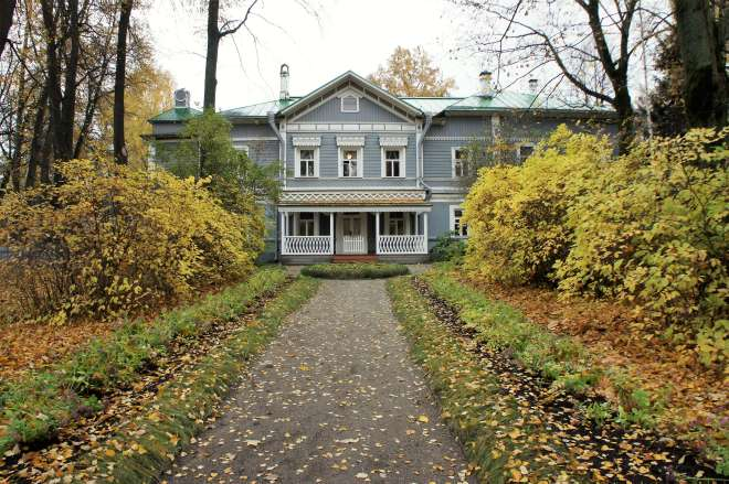 The Tchaikovsky House Museum is a grey wooden house at the end of a path covered in autumn leaves, with bushes on either side, covered in yellowing leaves.