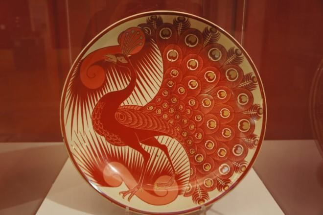 Large plate with a styalised red peacock design by William de Morgan