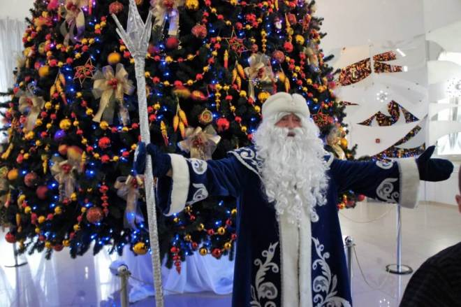 Ded Moroz stands in front of a decorated tree at the New Year and Christmas tree decorations factory in Klin. He is wearing a long blue coat with white patterns and fur trim, and large blue mittens and a white hat. He has a long white beard and outstretched arms, one of which is holding a tall white staff.