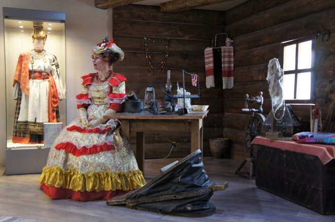 A seated woman in a long ornate red and gold frilly dress and an overdecorated hat explains the origins of the Klin glass factory while seated in a replica wooden peasant's house.