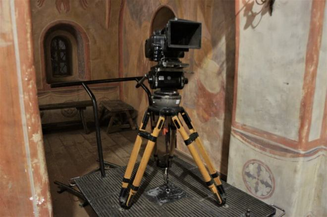 A large movie camera in a tripod stands in a set of a Russian Orthodox church at MosFilm Studio
