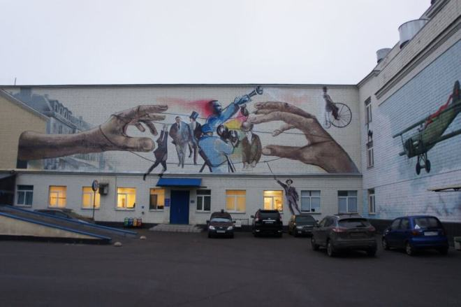 A mural showing two large hands pulling the strings of figures such as a cameraman, actors and musicians on a building at MosFilm Studio