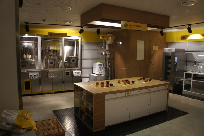 The interior of a tea factory with a kitchen island set up with small coloured tea bowls surrounded by various stainless steel tea processing machines