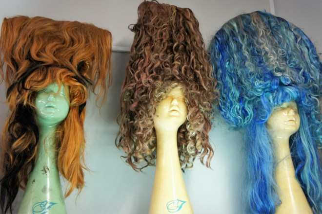 Three mannequin heads with large colourful curly haired wigs