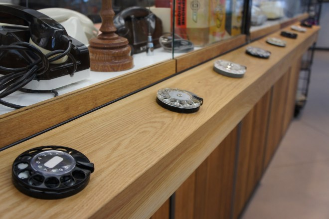 Telephone dials mounted on the back of a display case for visitors to touch and operate