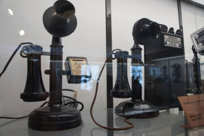 Early payphones, black candlestick model with a box to take coins on the side in a case with other vintage phones