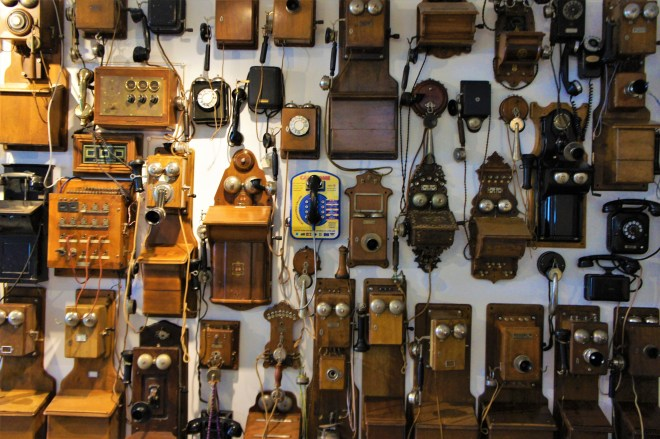 Lots of old telephones hanging on a wall.