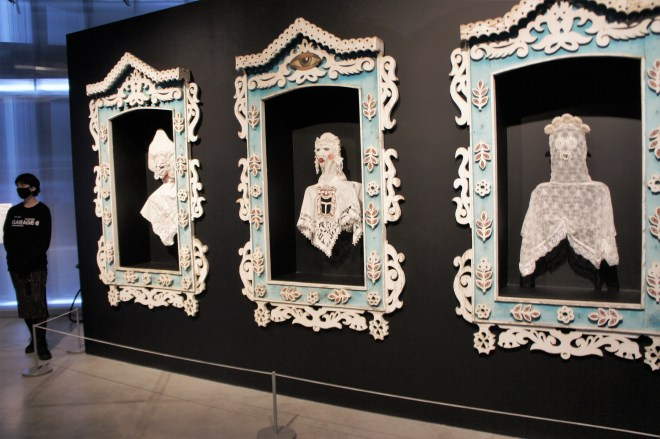 Three traditional carved wooden window frames with busts of women in traditional Russian costumes made of lace at the 2nd Garage Triennial