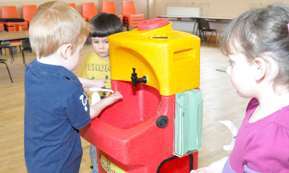Children learning how to wash hands with a portable handwash station