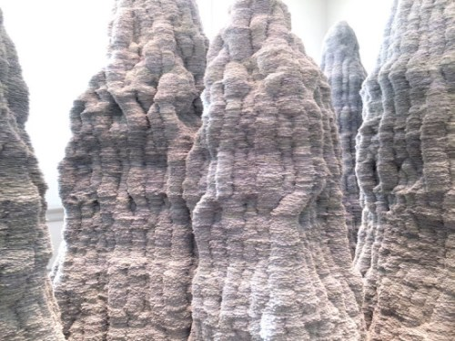 Stalagmite-esque sculptures by Tara Donovan are constructed of index cards