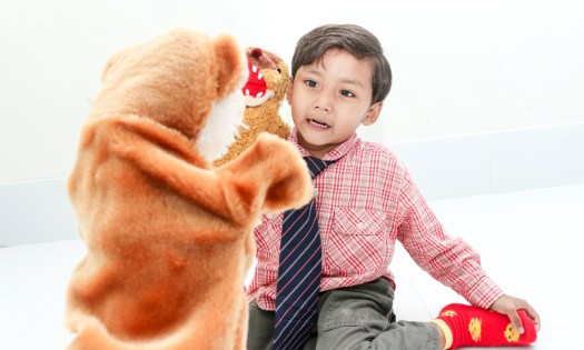 child playing with puppets