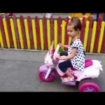Outdoor playground. Kids driving cars and motorcycles