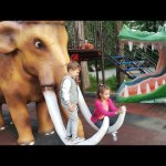 Outdoor playground fun for kids in the park.  Sliders with dinosaurs, mammoths, elephants…