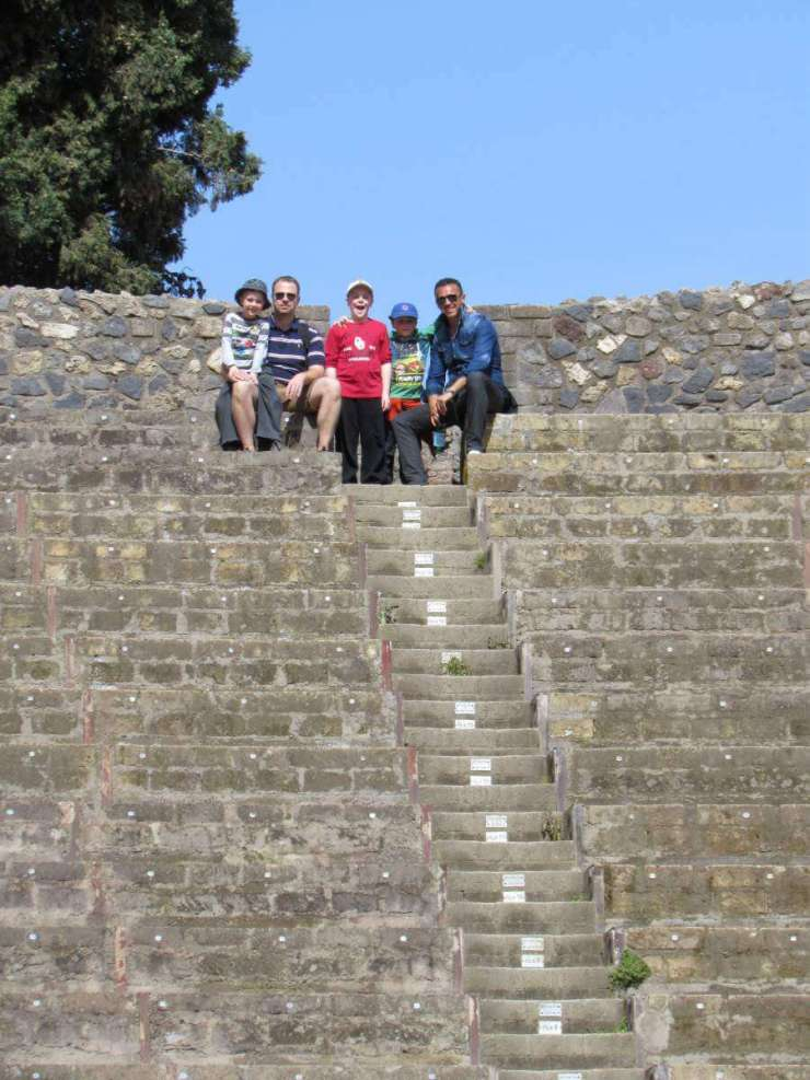 How to See Pompeii with Kids taking a break in the amphitheater- Kids Are A Trip