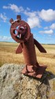 Image of metal owl sculpture on dry stone wall with corn field and blue sky behind