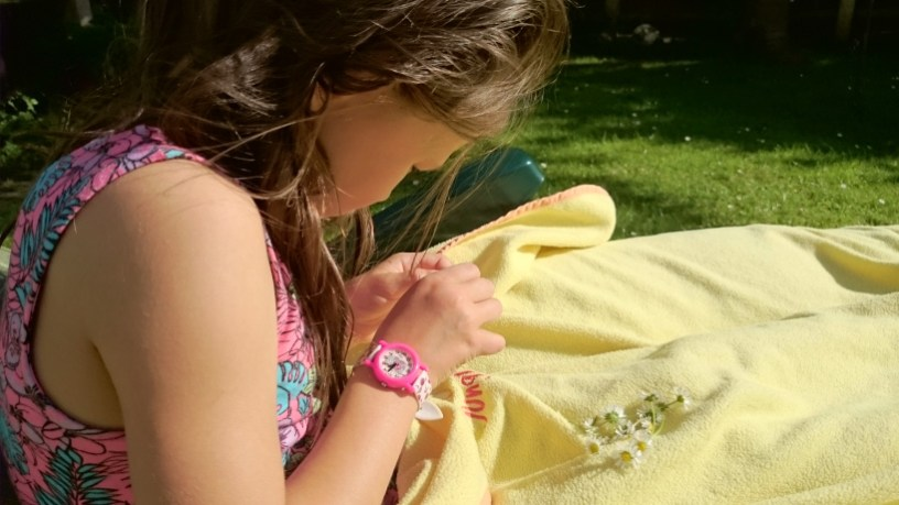 Image of girl in floral dress making daisy chains on yellow blanket on grass