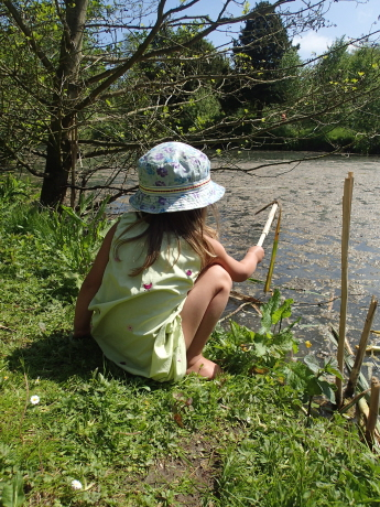 Image of grl in sunhat sat by river bank, dipping with stick