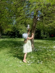 Image of barefoot girl in sunhat on grass reaching up to branches of a tree