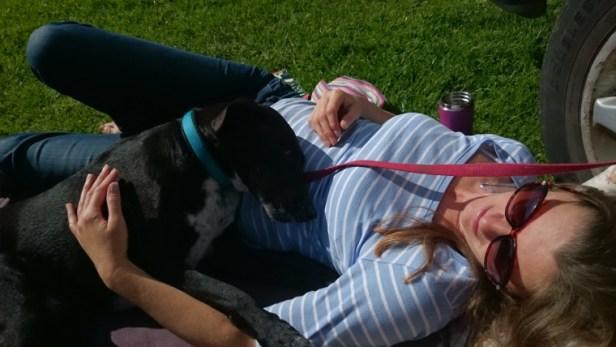 black-and-white-dog-lying-on-grass-cuddling-female-owner