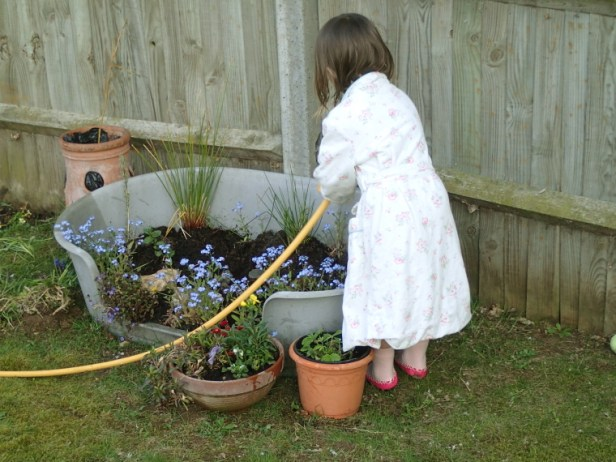 Child watering container garden with hose