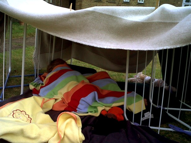 child-under-blanket-in-garden-den-made-of-blankets-and-clothes-airer