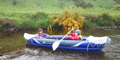 Image of children-in-inflatable-canoe-on-river