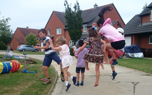 children-playing-street-jumping-over-rop
