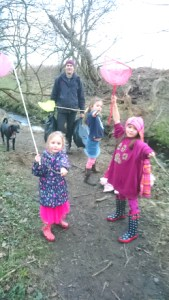 Image of children with fishing nets and man with plastic bags of litter by stream with dog