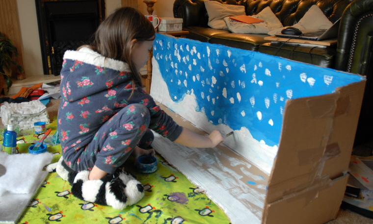 Image of girl-painting-snow-onto-a-box-scene