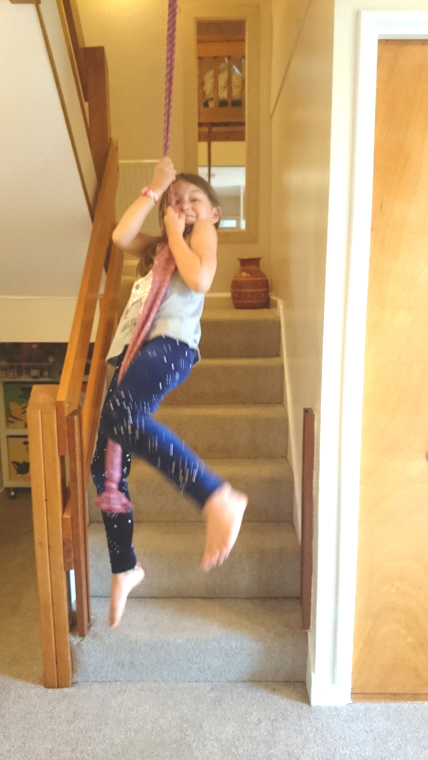 Image of girl-swinging-from-rope-over-stairs